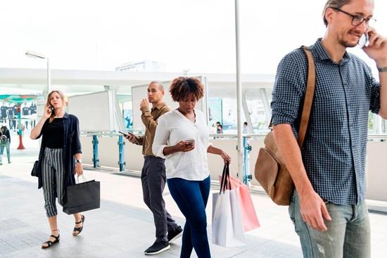 Photo de personnes à proximité de commerces de détail qui téléphonent, regardent leurs smatphones et font du shopping